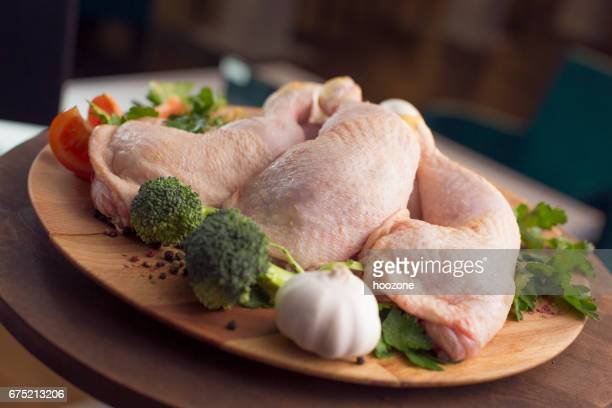 Raw chicken legs decorated with vegetables