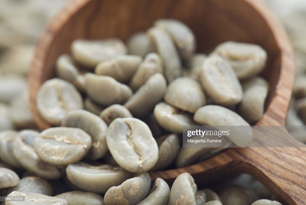 Raw coffee beans on wooden scoop