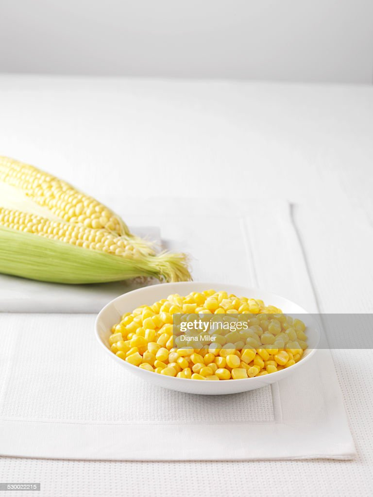 Raw corncobs on marble cutting board and bowl of boiled sweetcorn