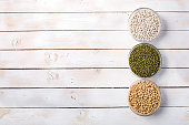 Raw mung beans, white beans and soybeans in glass bowls on white wooden background top view, space for text. Vegan protein source. Superfoods and Healthy food clean eating.
