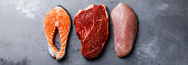 Raw food Salmon oily fish steak, beef meat and turkey breast on gray concrete background