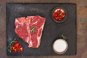 Raw T-bone steak with salt and rosemary. Top view, blank space