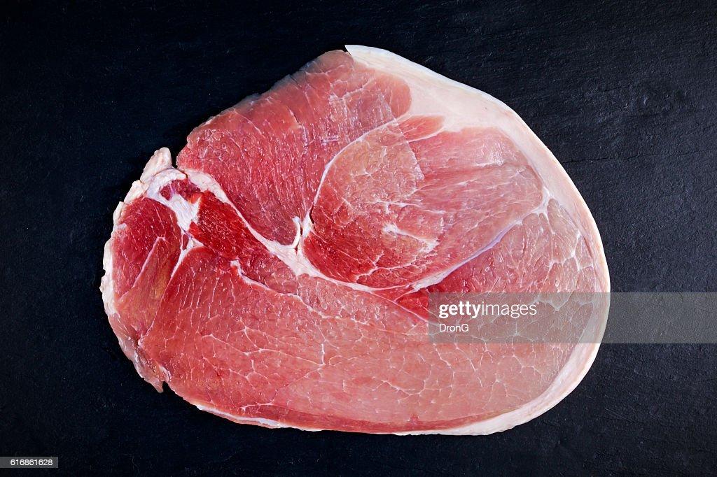 Raw gammon steak on black stone background : Stock Photo
