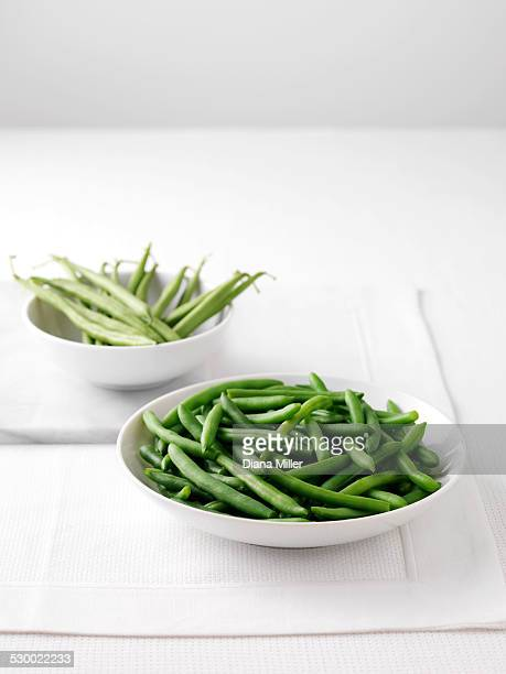 Raw green beans in bowl on cutting board and bowl of boiled green beans