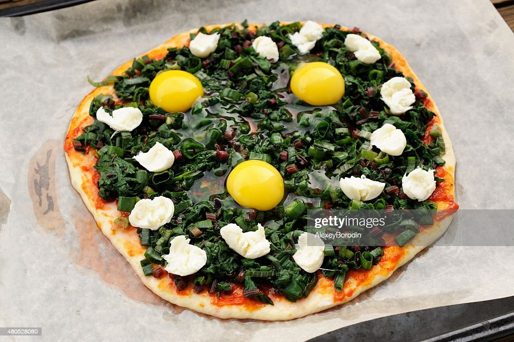 Raw green pizza with eggs and mozarella on baking paper : Bildbanksbilder