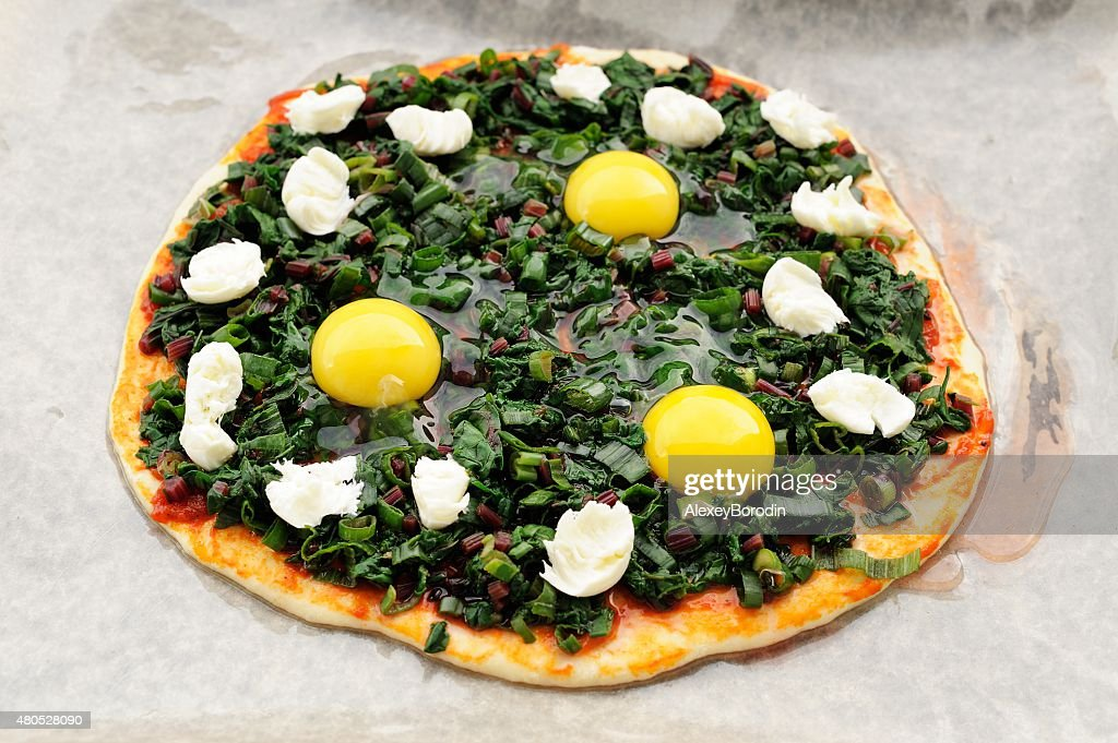 Raw green pizza with eggs and mozarella on baking paper : Stockfoto