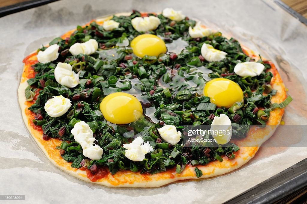 Raw green pizza with eggs and mozarella on baking paper : Stock Photo
