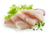 raw hake fish fillet pieces on a white background