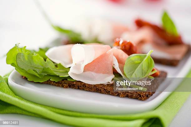 Raw ham, rocket and dried tomatoes on wholemeal bread, close-up