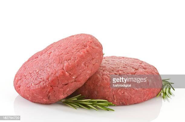Raw hamburger patties against white background