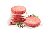 Two raw hamburger patties isolated white background. Predominant colors are red and white. Some cooking and seasoning ingredients like rosemary, garlic, peppercorns and oregano are around the burgers.