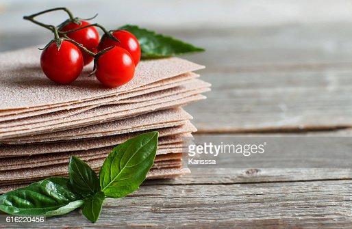 Raw lasagna sheets,basil and cherry tomatoes : ストックフォト