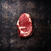 Raw fresh meat Ribeye Steak on dark metal background