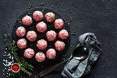 Raw meatballs on dark background, top view