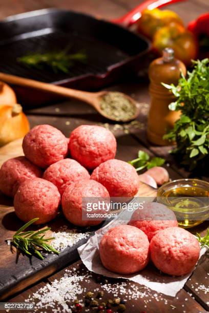 Raw meatballs on rustic wooden table