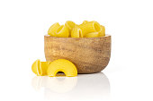 Lot of whole yellow raw pasta pipe rigate variety with wooden bowl isolated on white background