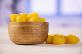 Lot of whole yellow raw pasta pipe rigate variety with wooden bowl with blue window