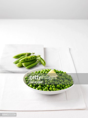 Raw pea pods on marble cutting board and bowl of boiled peas with butter