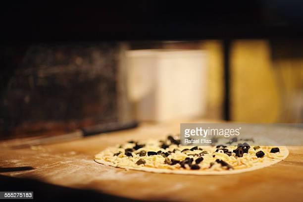 Raw pizza in kitchen