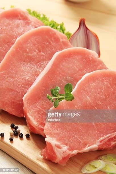 Raw pork chops on a wooden board