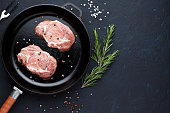 Raw pork chops on pan with rosemary, salt and pepper on stone background. Top view, copy space.