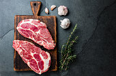 Raw pork cutlet chop for grill BBQ with herbs on wooden board, slate background, top view, copy spaces.