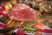 Raw pork shoulder on cutting board with knife.