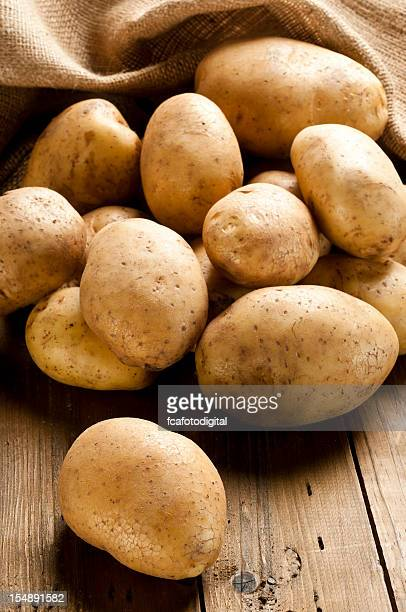 Raw potatoes out of a sack on rustic wood table