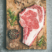 Flat-lay of raw prime beef meat dry-aged steak rib-eye on bone over rustic wooden board over grey concrete background with seasoning, top view, copy space, square crop. Meat high-protein meal concept