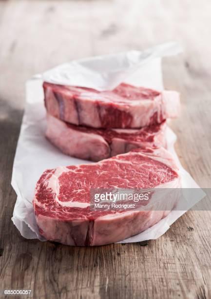 Raw rib eye steaks on butcher paper