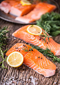 Salmon Fish..Raw salmon fillet pepper salt dill lemon rosemary on wooden table.Salmon Fish..Raw salmon fillet pepper salt dill lemon rosemary on wooden table.