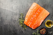 Raw salmon fillet and ingredients for cooking on a dark background. Top view