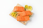 three raw salmon fillets, lemon and rosemary on cutting board
