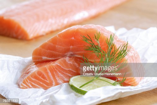 Raw salmon on foil with slice of lemon, close-up