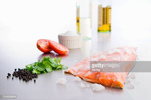 Raw salmon on stainless counter with ingredients