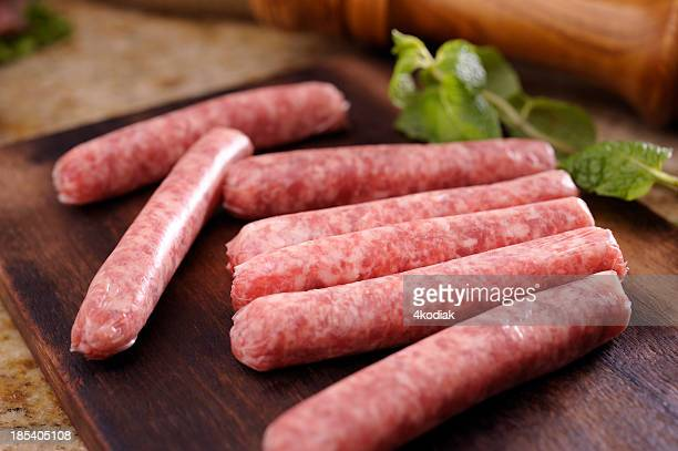 Raw sausages on wooden chopping block