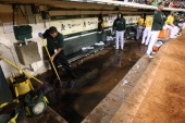 Raw sewage backs up in the Oakland Athletics dugout during the game against the Los Angeles Angels of Anaheim at Oco Coliseum on September 17 2013 in...