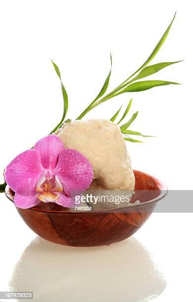 Raw du beurre de karité dans un bol en bois et en bambou et orchidée