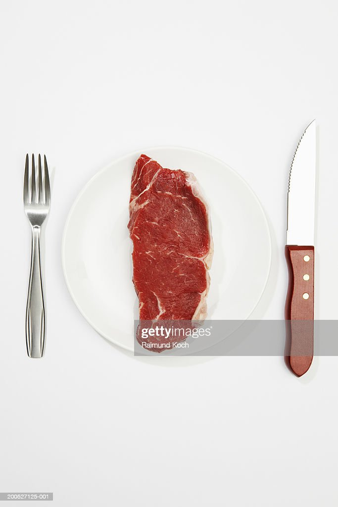 Raw steak on plate with knife and fork, white background, overhead view : Stock Photo