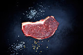 Raw striploin steak and salt