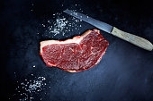 Raw striploin steak, salt and knife