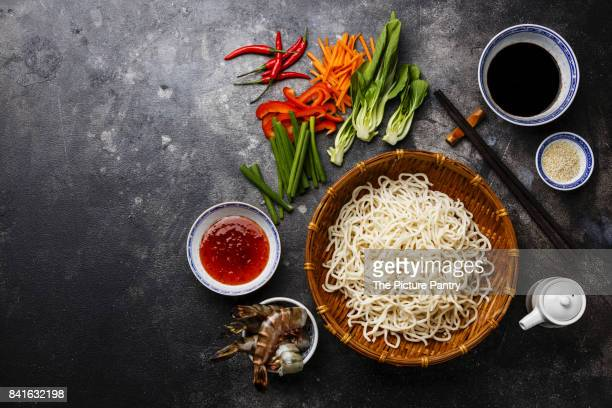 Raw Udon noodles in bamboo basket and Ingredients for cooking asian food with Tiger shrimps, greens, vegetables, spices on dark background copy space