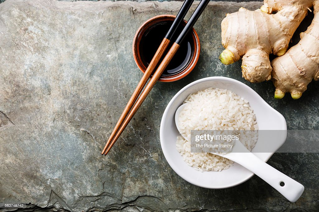 Raw white rice, fresh ginger root, soy sauce and sushi chopsticks on gray stone slate background