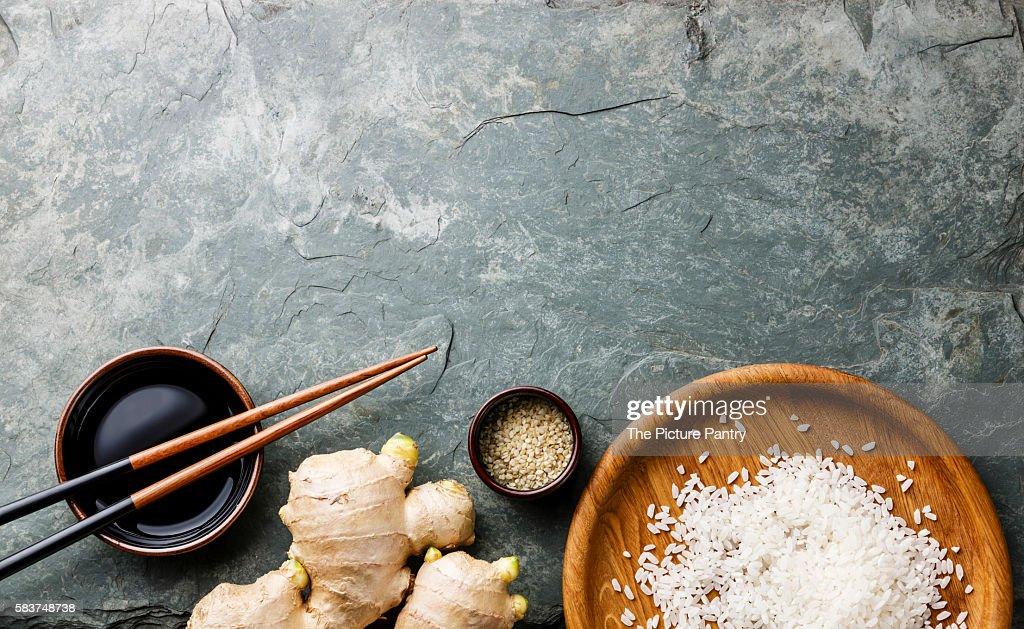 Raw white rice, ginger, soy sauce and sushi chopsticks on gray stone slate background