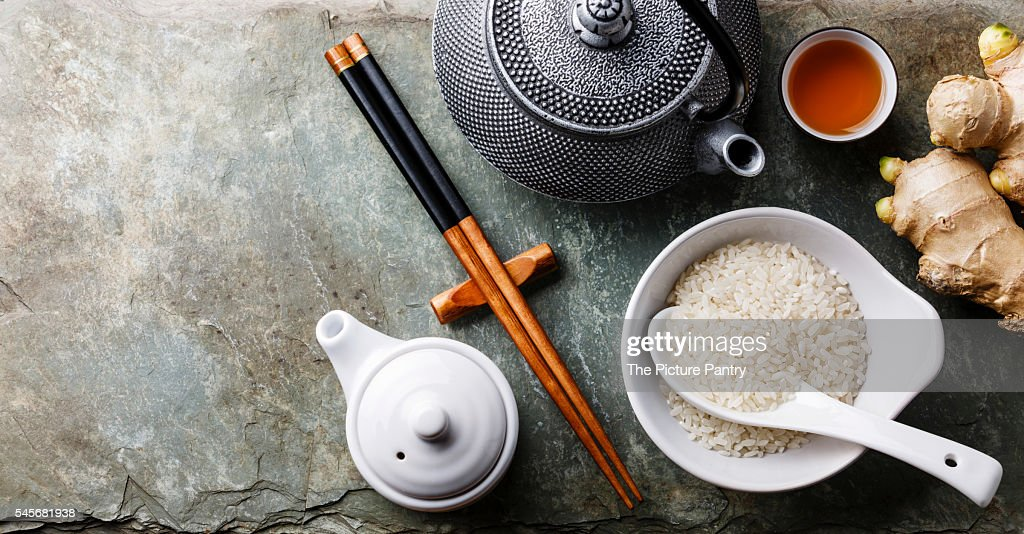 Raw white rice, green tea teapot, soy sauce and sushi chopsticks on gray stone slate background