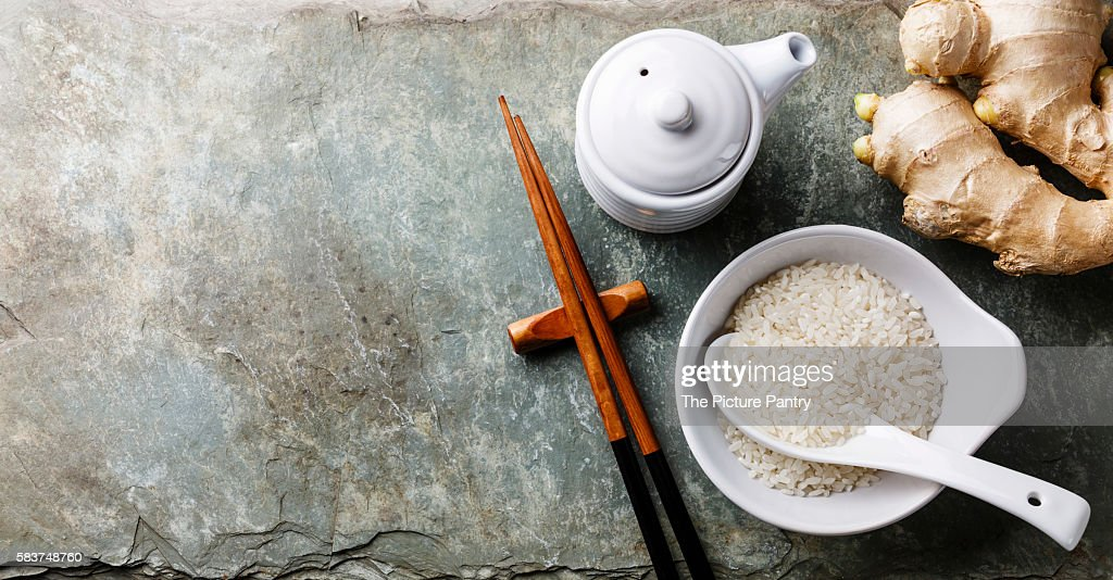 Raw white rice, soy sauce and sushi chopsticks on gray stone slate background