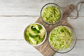 Different kind of raw zucchini noodles on the white wooden table top view