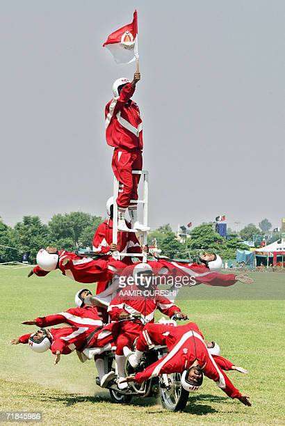 Pakistani army soldiers in colourful outfits show their acrobatic skills on a motorbike during celebrations of Pakistan's Defence Day in Rawalpindi...