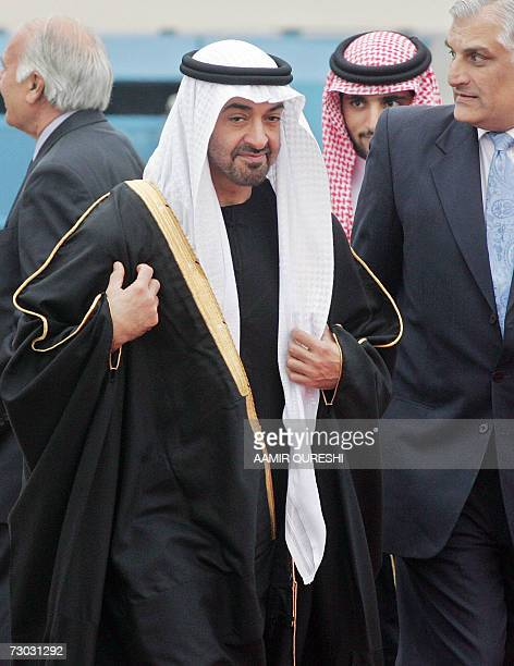 United Arab Emirates' Crown Prince Sheikh Mohammed Bin Zayed Al Nahyan adjusts his dress as he walks with Pakistani officials on his arrival at the...