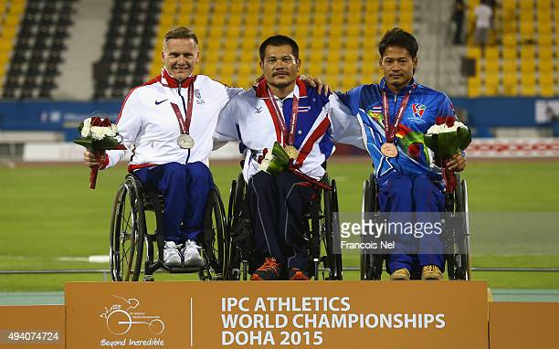 Rawat Tana of Thailand poses with his gold David Weir of Great Britain silver and Saichon Konjen of Thailand bronze after the men's 1500m T54 final...